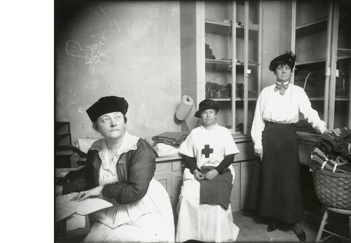 Three Red Cross worker,s one in a Red Cross smock