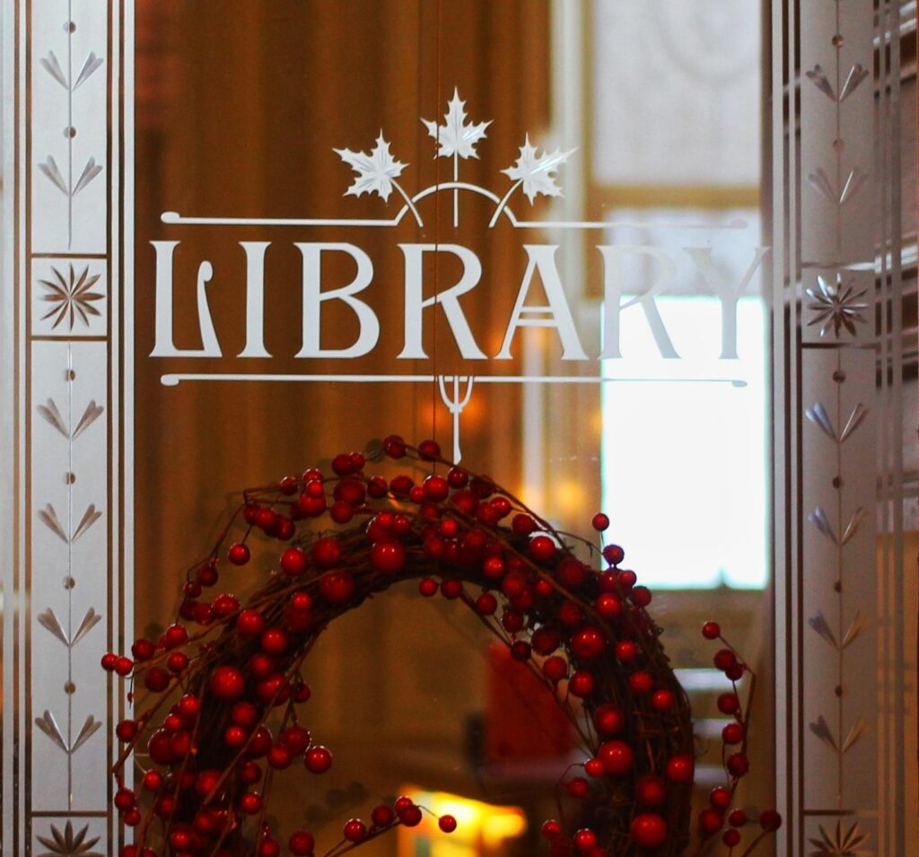 Photo of a library door with holiday decor.