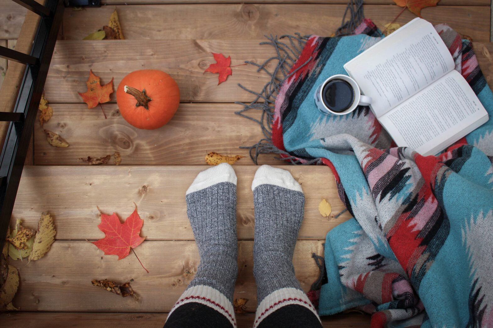 Fall image with book, pumpkin, and socked feet